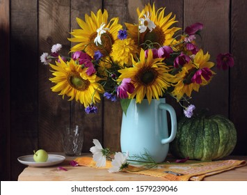 rustic still life with garden flowers: sunflowers and daisies, cornflowers and Golden balls. bouquet in a jug on the table, pumpkin and Apple.
