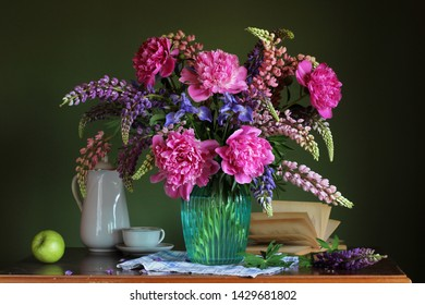 rustic still life with a lush bouquet of peonies, irises and lupins, an Apple and an open book. cultivated flowers in a glass vase on the table.