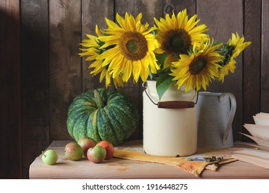 rustic still life with sunflowers and pumpkin on a plank background.