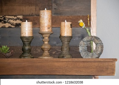 Rustic still life of wooden candle holders and candles and a flower sitting on a mantle against a reclaimed wood background