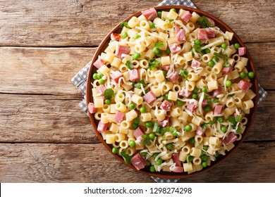 Rustic style Ditalini pasta with green peas, ham and cheese closeup on a plate on a wooden table. horizontal top view from above