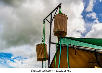 Rustic style, safari bucket shower, assembled beside canvas tent, at bush camp in Central Serengeti NP, Tanzania.The water bucket is attached to a pole with a pulley and rope. 20 litres of warm water.