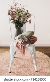 Rustic styled vase of flowers with wool scarves on a white chair