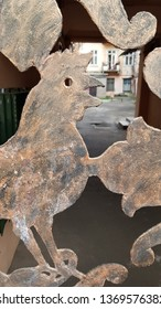 Rustic styly rooster cutout silhouette with open beak on blurred background of old courtyard buildings. Decorative elements of aged metal fake bronze gates. Cutout ornaments closeup. Grunge textures