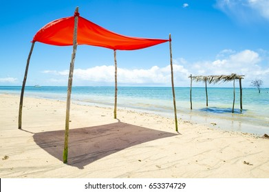 Rustic sun shade made from a sheet strung from sticks stands on an empty beach in Bahia, Brazil