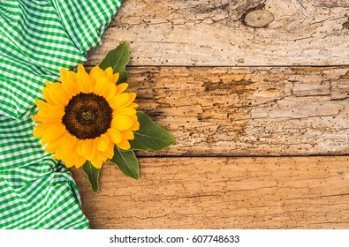 Rustic Sunflower Blossom On Old Wooden Background With Green White Checkered Fabric Decoration