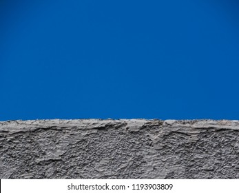 rustic surface wall painted in white color, contrasting with the color and homogeneous surface of the blue sky, sao paulo, brazil