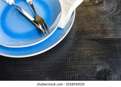 Rustic table setting with ceramic plates, napkin and silverware on dark wooden table