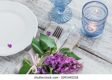Rustic table setting with lilac flowers on light wooden table. Wedding table decoration on Provence style. Romantic dinner.