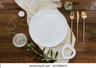 Rustic table setting on wooden table: gold vintage silverware, linen napkin and olive brunch. Romantic or wedding concept