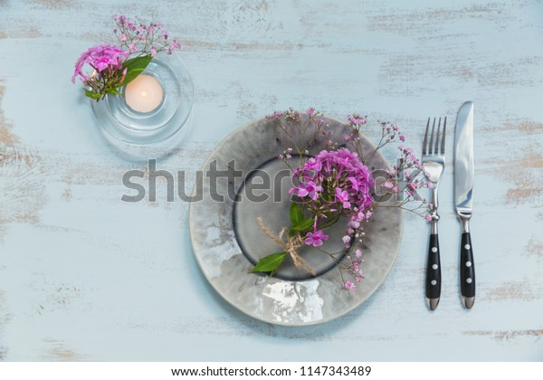 Rustic table setting with pink flowers and candle on light wooden table. Holidays decoration on Provence style. Romantic dinner. Top view