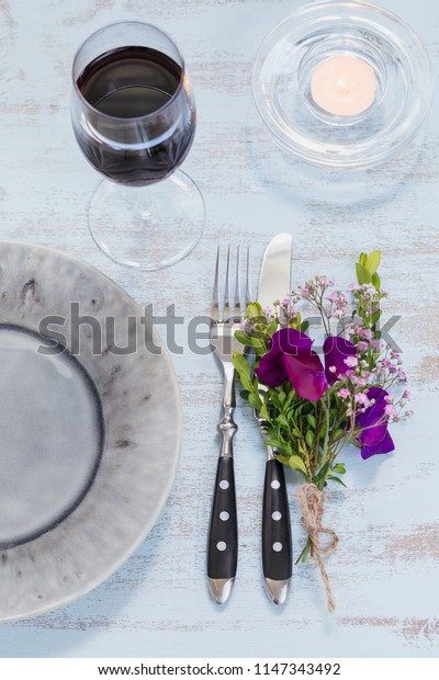 Rustic table setting with purple flowers, candle and a glass of red wine on light wooden table. Holidays decoration on Provence style. Romantic dinner. Top view