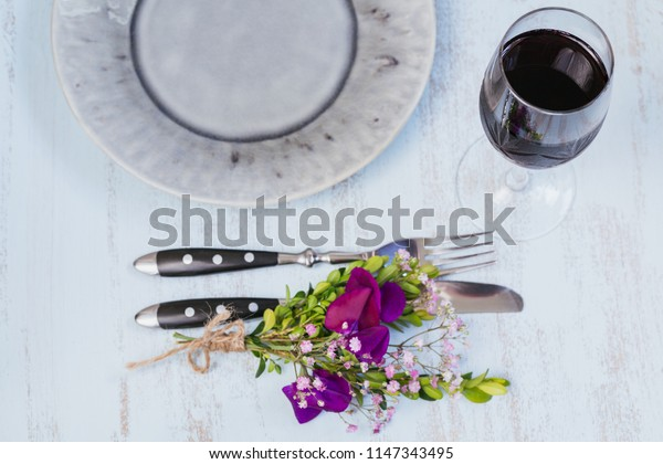 Rustic table setting with purple flowers and glass of red wine on light wooden table. Holidays decoration on Provence style. Romantic dinner. Top view