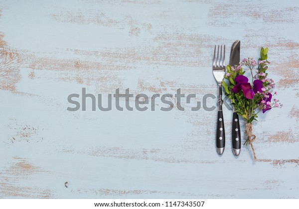 Rustic table setting with purple flowers on light wooden table. Holidays decoration on Provence style. Romantic dinner. Top view with copy space for text