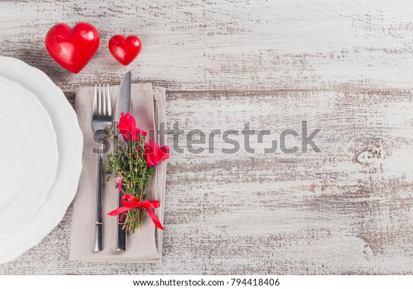Rustic table setting with thyme and cyclamen flowers and shape of heart decoration on light wooden table with copyspace. Valentine's day holiday decoration on Provence style. Romantic dinner.