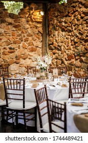 Rustic table setting at wedding reception with wooden tiffany chairs. Selective Focus.