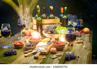 Rustic table with snacks and wine in illuminated garden