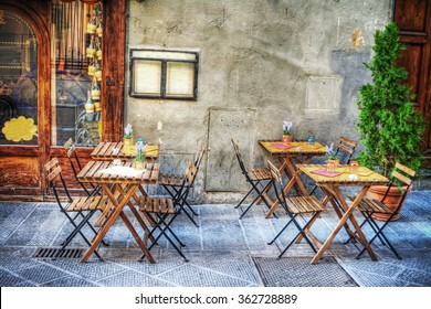 rustic tables and chairs by a trattoria in Florence, Italy