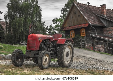 Rustic tractor and house on a cloudy day