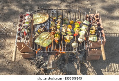 Rustic vegan barbecue made with recycled bricks. Cooking skewers and vegetables on the fire during a sunny day in the countryside.