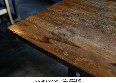 A rustic vintage old weathered brown wooden table with glass stain on concrete floor with blurred background