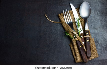 Rustic vintage set of cutlery knife, spoon, fork. Black background. Top view