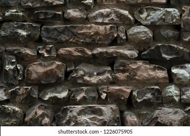 Rustic wall made of irregular rock blocks
