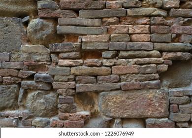 Rustic wall made of irregular stones and bricks