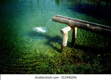Rustic water feature with water running out of a hollow log into a tranquil pond below in a simple waterfall, high angle view