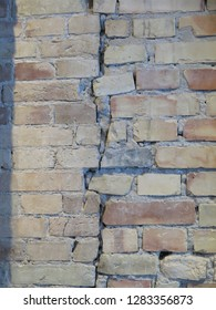 Rustic weathered exposed brick wall on village road in Andalusia