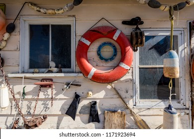 Rustic and weathered nautical items used as décor hanging on an old building outer wall.