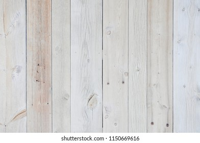 Rustic weathered wood surface with long boards lined up. Wooden planks on a wall or floor with grain and texture. Multicolor background with light bleached flat neutral tones.