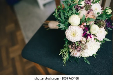 Rustic wedding bouquet with white dahlias, peonies, and greens on a dark chair. Artwork