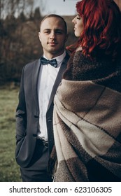 rustic wedding couple posing and standing at background of wooden barn. wedding concept, space for text. happy stylish bride in blanket and groom at wood wall in country, bohemian newlyweds