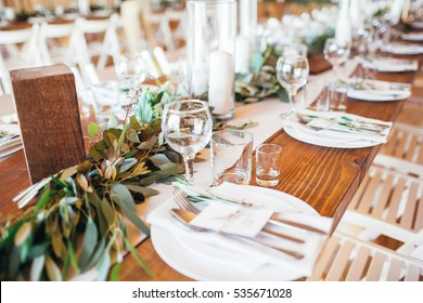 Rustic wedding decor, wedding table setting with candles and eucalyptus.