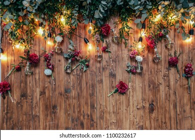 Rustic wedding photo zone. Hand made wedding decorations includes Photo Booth  red flowers. Garlands and light bulbs