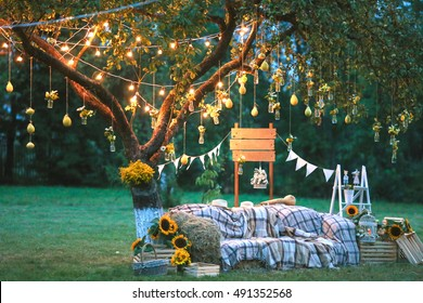 Rustic wedding photo zone. Hand made wedding decorations includes Photo Booth, wooden barrels and boxes, lanterns, suitcases and white flowers