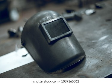 A rustic well worn gritty industrial welders mask in an atmospheric factory setting. Moody atmospheric lighting. Post apocalyptic headwear.