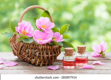 Rustic wicker basket with pink rose hip flowers and bottles of essential roses oil.