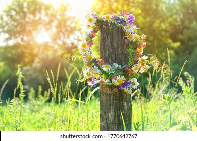 rustic wildflowers wreath in garden, sunny day. Farm lifestyle. Summer Solstice Day, Midsummer. floral traditional decor. pagan witch traditions, wiccan symbol and rituals.