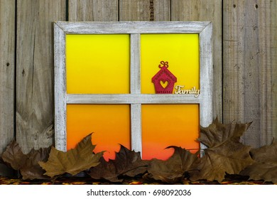 Rustic window with blank colorful window panes with red house with heart and the word Family by fall leaves border with aged wood background; seasonal, home and nature background with copy space