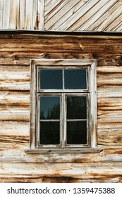 Rustic window in wooden village cottage house. Grunge brown wood wall background.