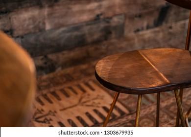 Rustic wood and bronze metal bar stools. Close up details. Coffee shop, home loft interior design, minimalism concept