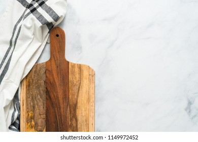 Rustic wood cutting board on marble countertop.