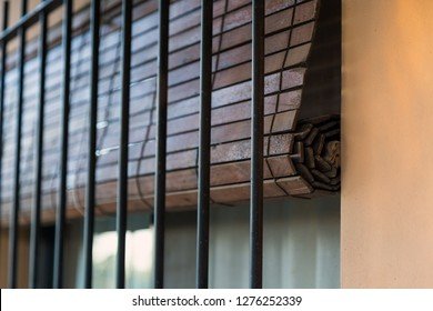 Rustic wood roller blind. Window with blind and iron bars.