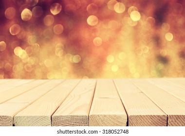 rustic wood table in front of glitter silver and gold bright bokeh lights. filtered image