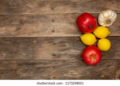 Rustic wood table with lemons garlic apple pomegranate