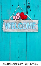 Rustic wood welcome sign with red fabric hearts and black iron skeleton keys hanging on teal blue antique wooden background