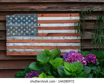 Rustic wooden American flag on the side of a weathered building, with flowers in the foreground.
