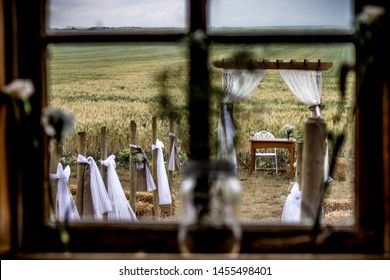 Rustic wooden arbor at a vintage country wedding looking through a barn window with the wedding aisle in front of a wheat field on a farm with a storm in the sky